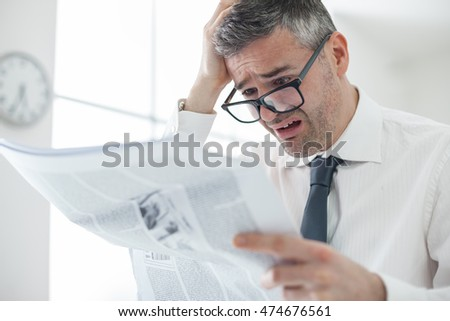 Businessman in the office, reading bad breaking news on a business newspaper, he is in panic and touching his head, financial crisis concept
