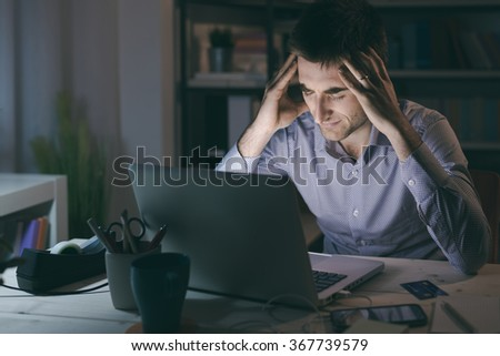 Businessman in the office working late at night and having a bad headache, overwork and stress concept