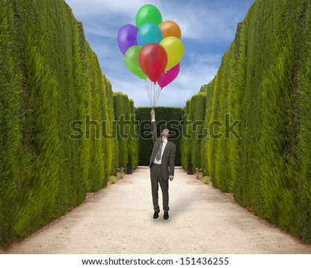 Businessman in the park holds the inflated balloons  - stock photo