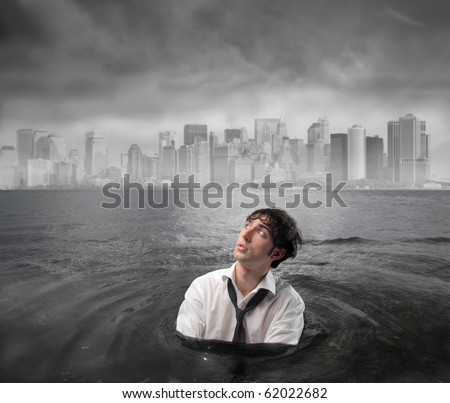 Businessman in the water with cityscape under stormy sky on the background
