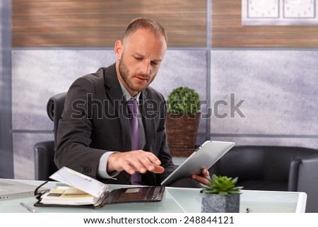 Businessman in trouble between tablet computer and personal organizer, sitting in office. - stock photo