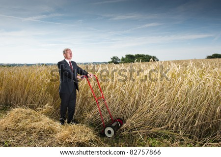 Businessman in Wheat Field. Man in a dark business suit cutting down wheat in a farm field. Metaphor for harvesting the fruits of your labor - stock photo