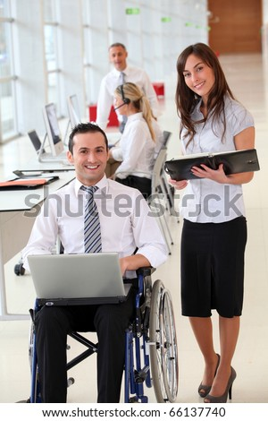 Businessman in wheelchair with assistant in office - stock photo