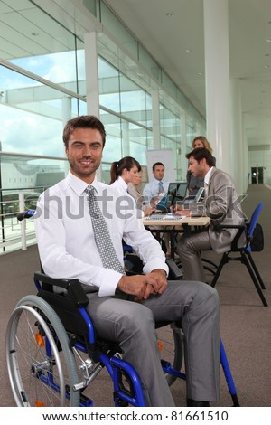 Businessman in wheelchair with colleagues in background - stock photo