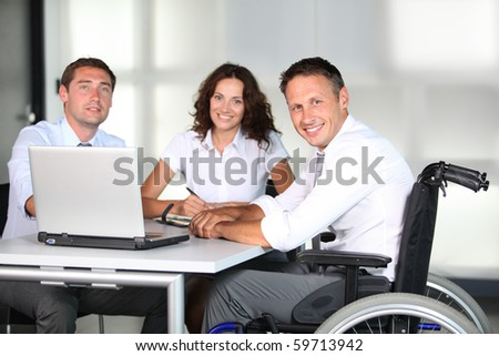 Businessman in wheelchair working in the office with colleagues - stock photo
