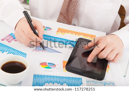 Businessman in white shirt analyzing graphs and charts - stock photo