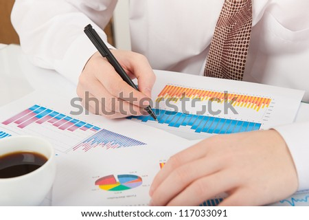 Businessman in white shirt and necktie analyzing graphs - stock photo