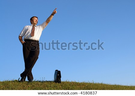 Businessman in white shirt and tie standing with crossed legs in grass field against clear blue sky pointing up
