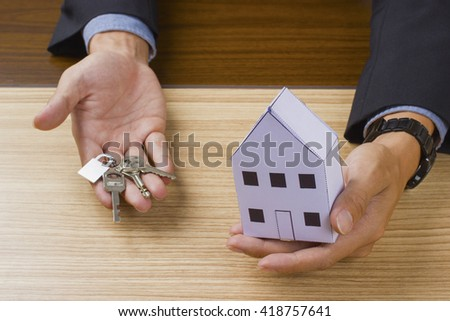 businessman in white shirt holding a small house and apartment keys in hand - stock photo