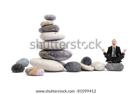 Businessman in yoga position on a pebble composition - stock photo