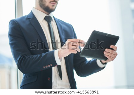Businessman indicates a ballpoint pen on the tablet which holds in his hand