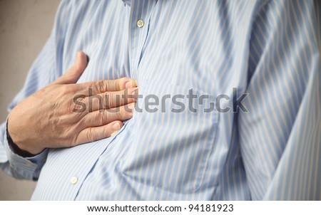 businessman indicates where he feels discomfort from heartburn - stock photo