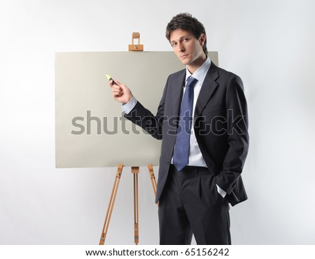 Businessman indicating a point on a blackboard - stock photo