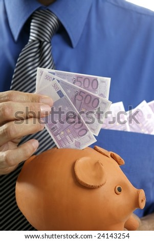 businessman insert euro notes in clay piggy bank - stock photo