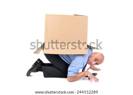 Businessman inside a cardboard box - stock photo