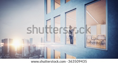 Businessman inside skyscraper, lookng at the city through  window - stock photo