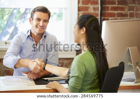Businessman Interviewing Female Job Applicant In Office - stock photo