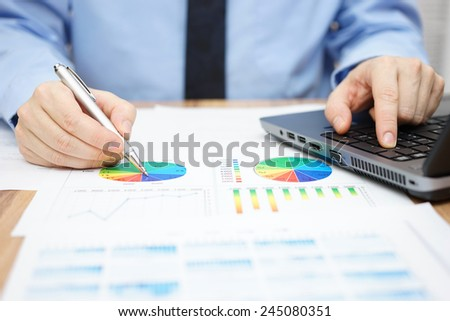 businessman is analyzing business data and using laptop - stock photo