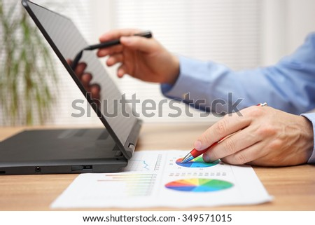 businessman is analyzing business data  on document and working with  stylus pen on touchscreen laptop computer - stock photo