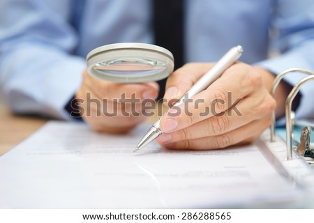 businessman is analyzing  through  magnifying glass contract and prices - stock photo