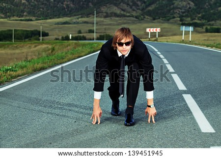 Businessman is at the start of running on the highway. Business struggle concept. - stock photo