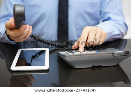 businessman is calling support when reading report on tablet computer - stock photo