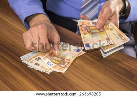 Businessman is counting euro banknotes, business and financial background - stock photo