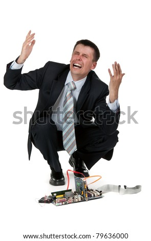 businessman is crying over the broken computer on a white background - stock photo