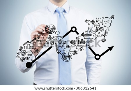 Businessman is drawing a growing arrow on the glass screen. Business icons as an integral part of the growing graph. - stock photo