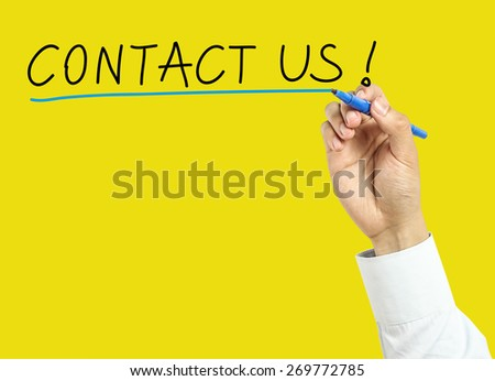 Businessman is drawing contact us concept with marker on transparent board with yellow background. - stock photo