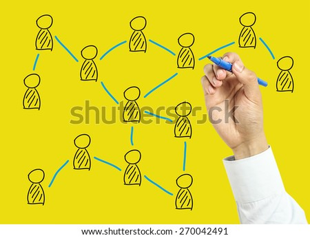 Businessman is drawing social network concept with marker on transparent board with yellow background. - stock photo