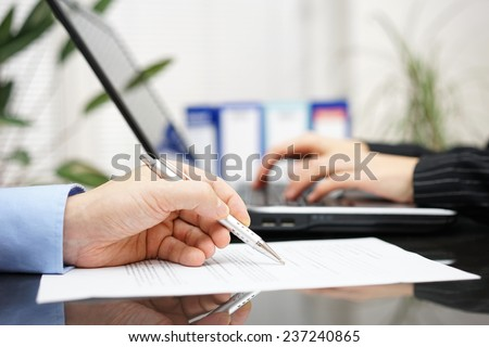 businessman is examine document and woman is working on laptop computer in background - stock photo