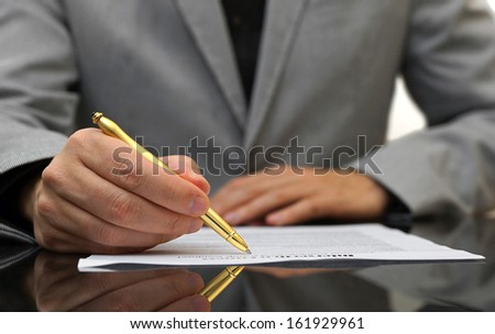 businessman is fulfilling and signing contract - stock photo