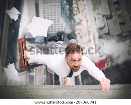 Businessman is going to fall from a skyscraper - stock photo