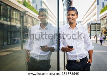 Businessman is holding a mobile phone and looking at camera. Shallow depth of field. - stock photo