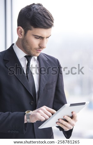 Businessman is holding a tablet in the office - stock photo