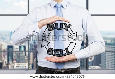 Businessman is holding a trading concept in his hands. City view office. - stock photo