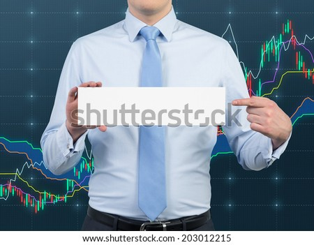 Businessman is holding a white empty rectangular table. The background is a forex huge wall screen. - stock photo