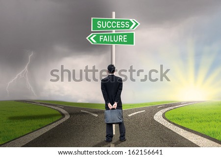 Businessman is holding briefcase and standing on the road with a sign of success or failure - stock photo