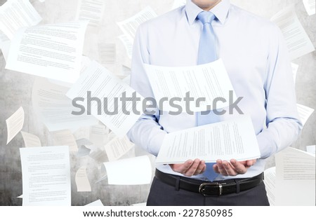 Businessman is holding documents which are scattered in the air over the sky background.