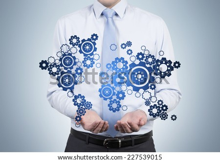 Businessman is holding in a palms the world map with gears. - stock photo