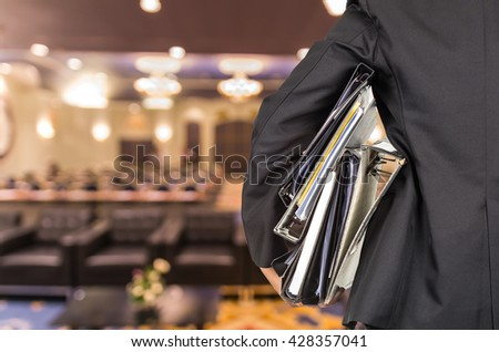 Businessman is holding many document folders on Abstract blurred photo of conference hall or seminar room background, back side, business busy concept - stock photo