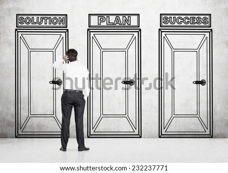 Businessman is making a choice of the three doors. - stock photo