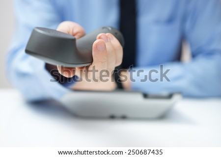 businessman is offering telephone handset - stock photo