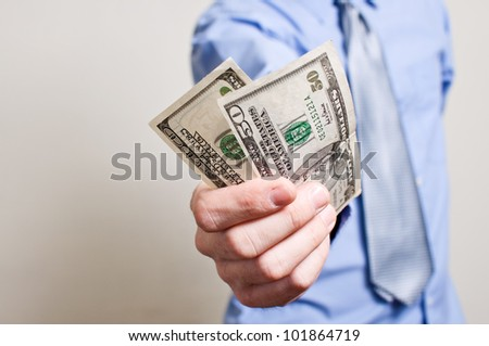 Businessman is paying in dollar bills, corruption and bribe concept. - stock photo