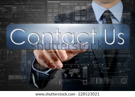 businessman is pressing a button with the inscription: Contact Us , in background are some graphs and diagrams - stock photo