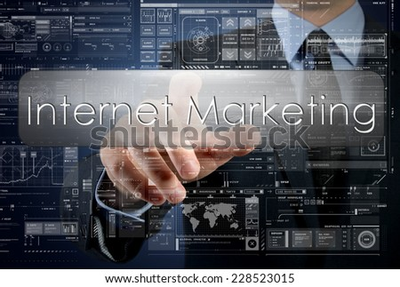 businessman is pressing a button with the inscription: Internet Marketing , in background are some graphs and diagrams - stock photo