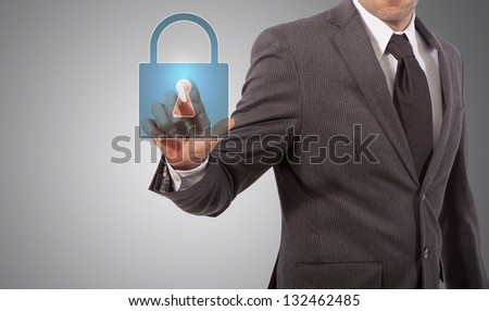 Businessman is pressing the security icon, grey background - stock photo