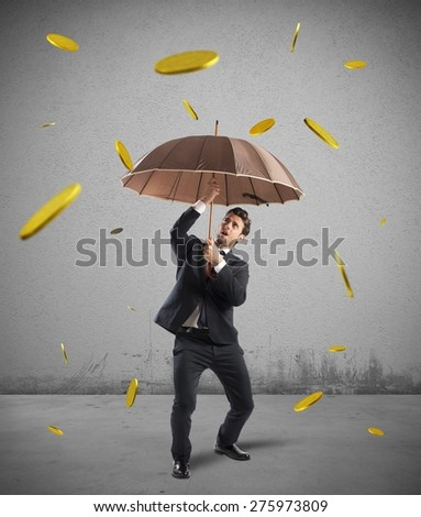 Businessman is protected by a money rain - stock photo