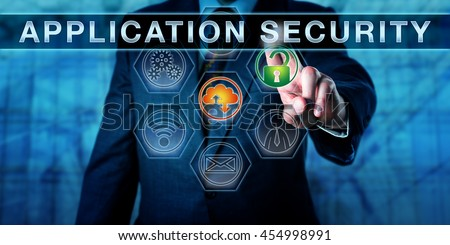 Businessman is pushing APPLICATION SECURITY on an interactive control screen. Computer security and information technology concept. Business metaphor. Close up torso shot of manager in blue suit. - stock photo